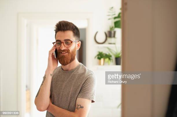 Young hipster man using a smart phone in his kitchen