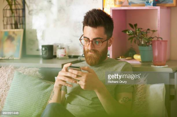 Young hipster man using a smart phone in his living room