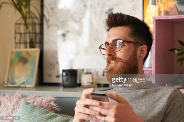 Young hipster man using his smart phone in his living room