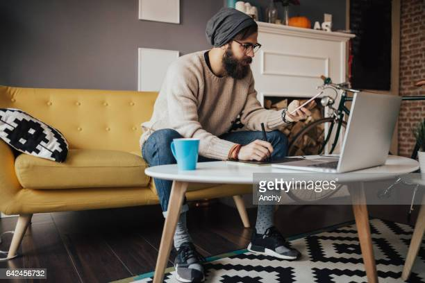 Young hipster man using multiple electronic portable devices