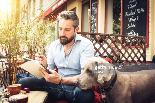 Young hipster man with dog sketching in street cafe