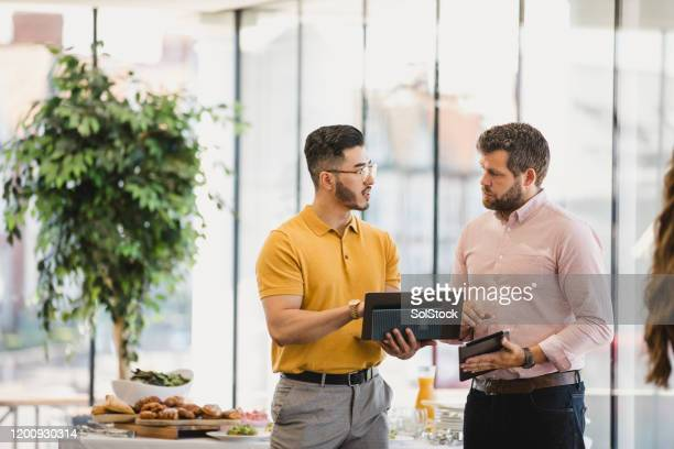 young hipster man with laptop discussing with coworker - business meeting stock pictures, royalty-free photos & images