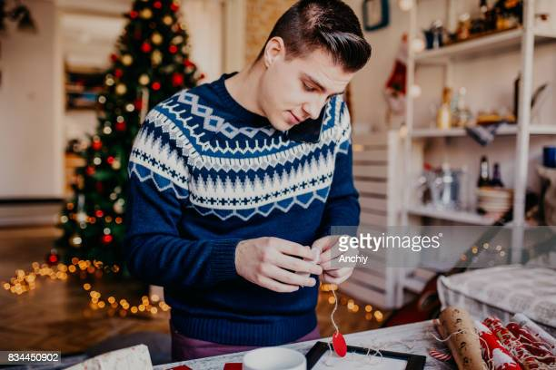 Young hipster man wrapping gift for his girlfriend