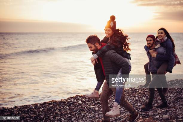 Young hipster men carrying girlfriends at the beach at sunset