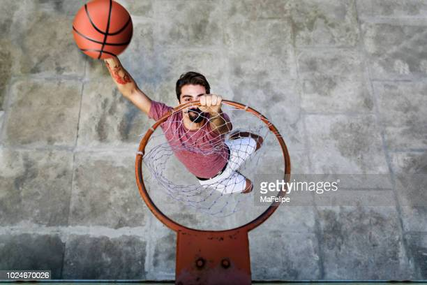 young hipster player dunking basketball in the hoop - taking a shot sport stock pictures, royalty-free photos & images