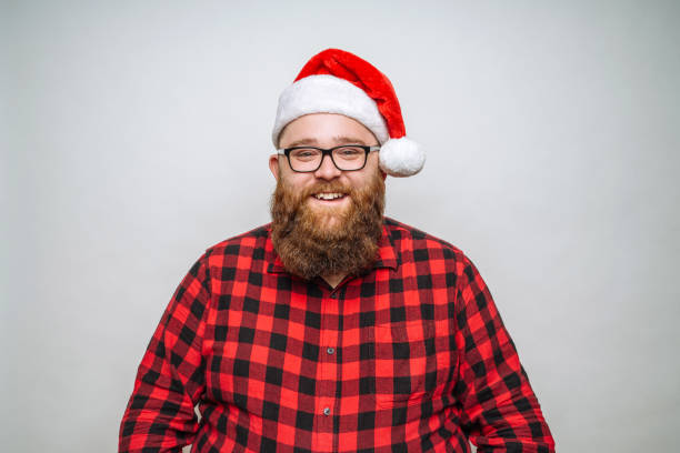young hipster santa claus wearing plaid shirt - fat santa stock pictures, royalty-free photos & images