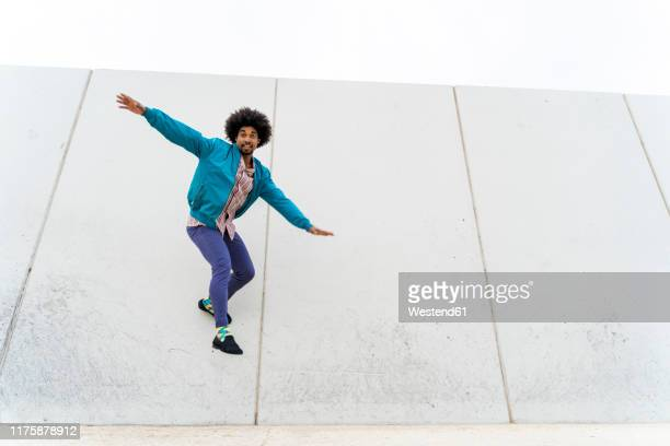 young hipster sliding on a white wall - skating stock pictures, royalty-free photos & images