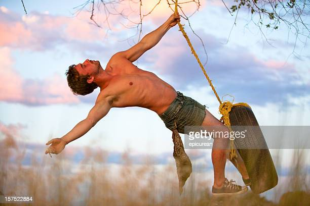 Young hipster swinging on rope swing at sunset