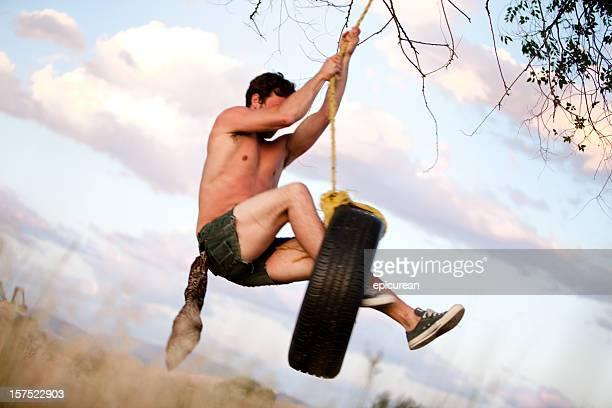 Jeune hipster se balancer sur la corde swing au coucher du soleil