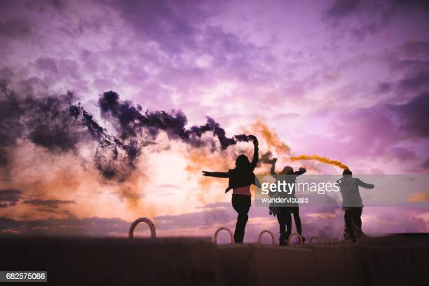 Young hipster teenagers celebrating with smoke bombs