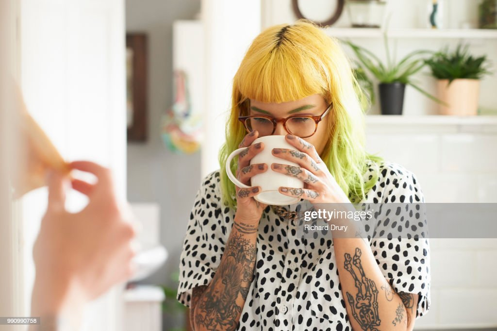 Young hipster woman drinking from a mug in her kitchen : Stock Photo