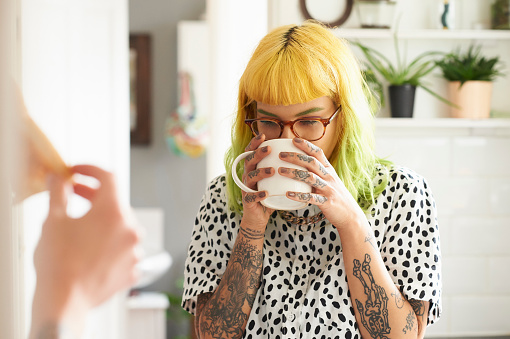 Young hipster woman drinking from a mug in her kitchen - gettyimageskorea