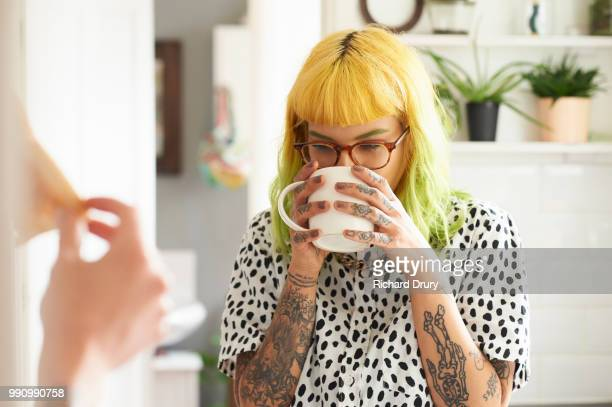 young hipster woman drinking from a mug in her kitchen - asian drink stock photos and pictures