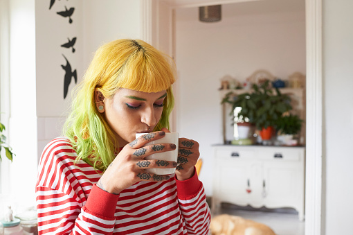 Young hipster woman drinking tea from a mug - gettyimageskorea