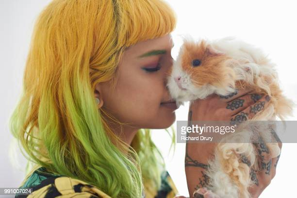 Young hipster woman embracing her pet guinea pig
