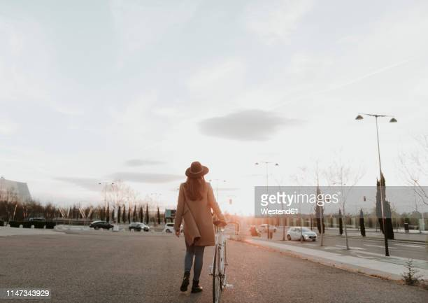 young hipster woman going with a bicycle during sunset - coat stock pictures, royalty-free photos & images