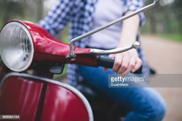 Young hipster woman in helmet sitting on a vintage scooter .