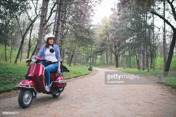 young hipster woman in helmet sitting on a vintage scooter . - moped stock photos and pictures