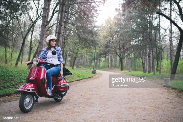 mulher jovem hippie no capacete sentado em um scooter vintage. - moped - fotografias e filmes do acervo