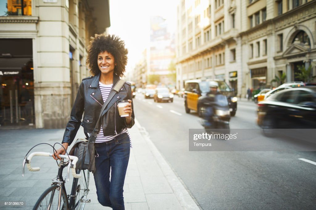 Young hipster woman in the streets of Barcelona commuting. : Stock Photo