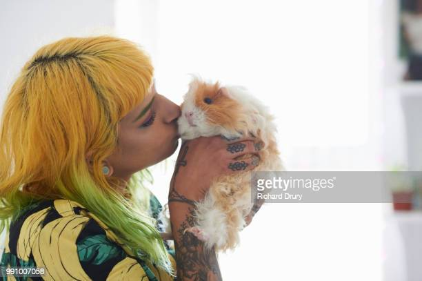 Young hipster woman kissing her pet guinea pig