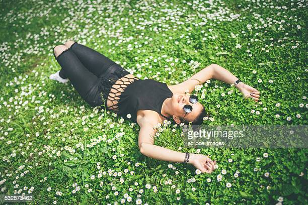 young hipster woman lying on a meadow