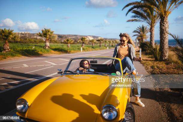 Young hipster woman on road trip vacations entering convertible car