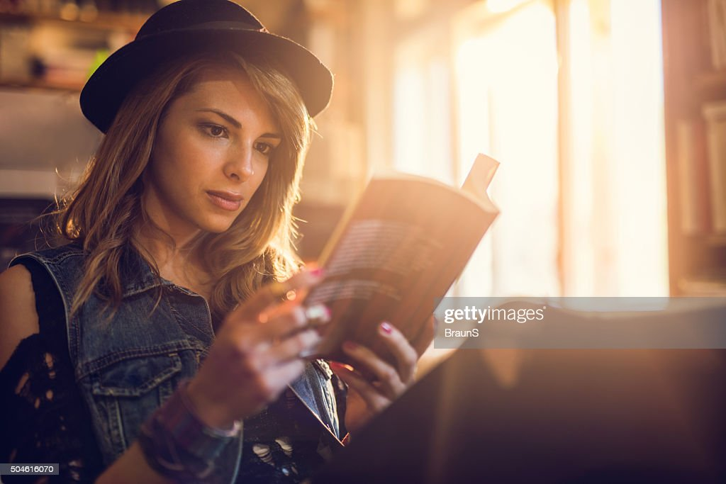Young hipster woman relaxing while reading a book. : Stock Photo