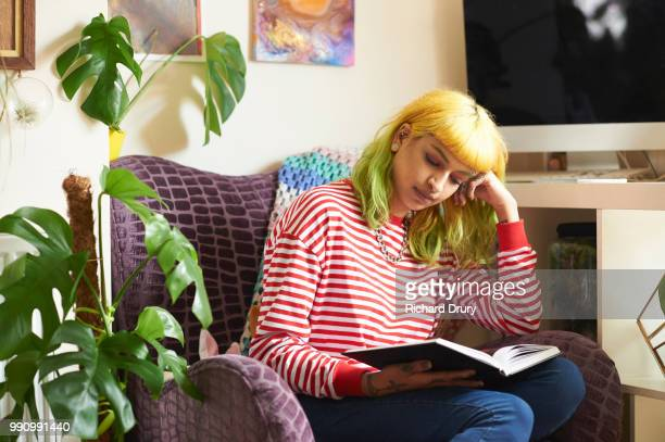 Young hipster woman sitting in an armchair reading a book