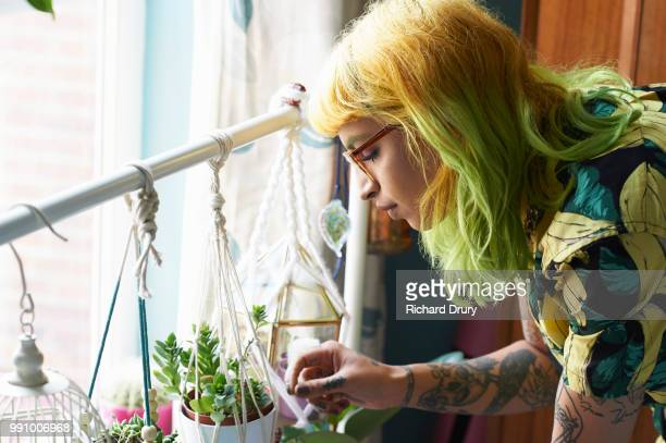 Young hipster woman tending to her succulent house plants