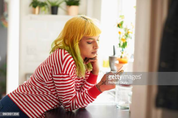Young hipster woman using a smart phone in her kitchen