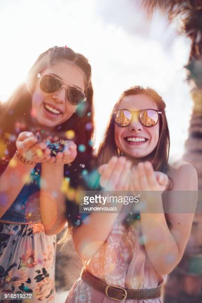Young hipster women celebrating with confetti on summer holidays