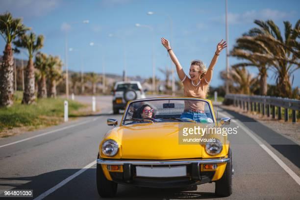 jonge hipster vrouwen converteerbare oldtimers rijden op road trip - cyprus stockfoto's en -beelden