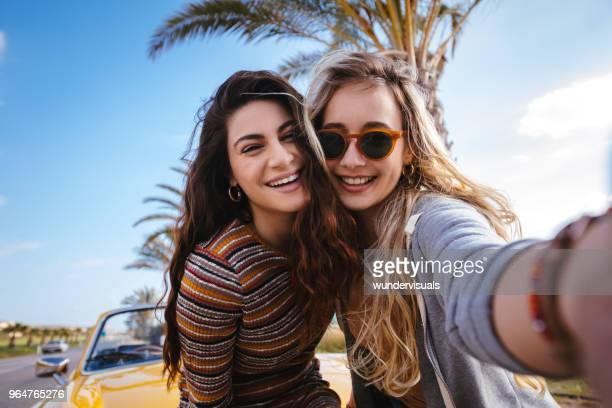 Young hipster women on road trip having fun taking selfies