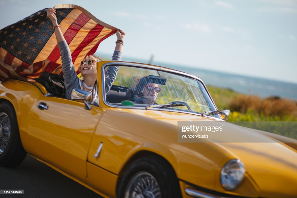 Young hipster women with American flag driving retro convertible car : Stock Photo