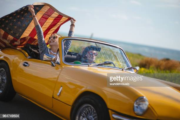 Young hipster women with American flag driving retro convertible car