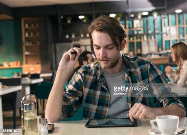 Young hipster working on tablet and smoking electronic ciggarette in restaurant