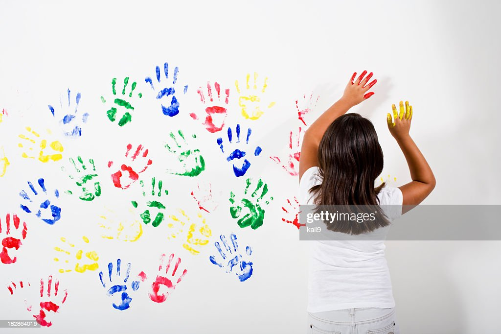 Young Hispanic Asian girl playing with finger paints : Stock Photo
