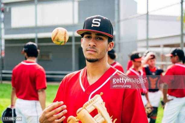 Young Hispanic baseball player tossing ball with confidence