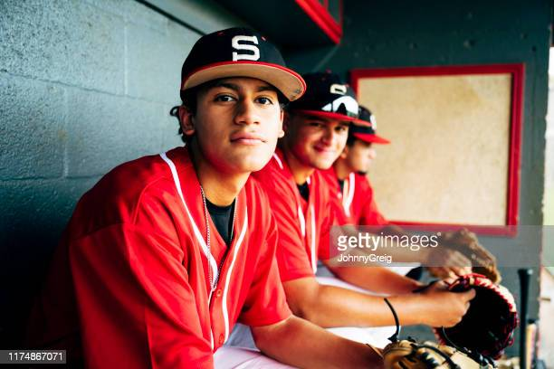 young hispanic baseball players sitting on bench in dugout - sideline stock pictures, royalty-free photos & images