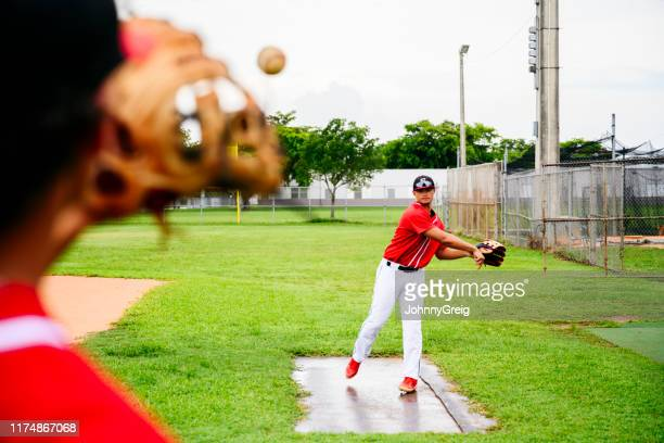 若いヒスパニック系野球選手が試合前にウォーミングアップ - 高校野球 ストックフォトと画像