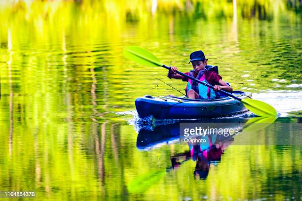 young hispanic boy kayaking - ogphoto stock photos and pictures