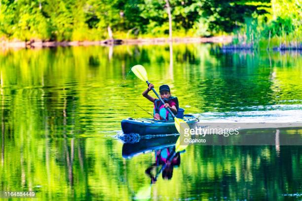 joven niño hispano en kayak - ogphoto fotografías e imágenes de stock