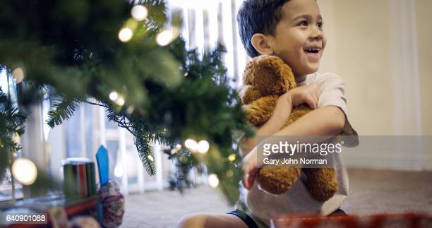 Young hispanic boy opening gifts under Christmas tree.