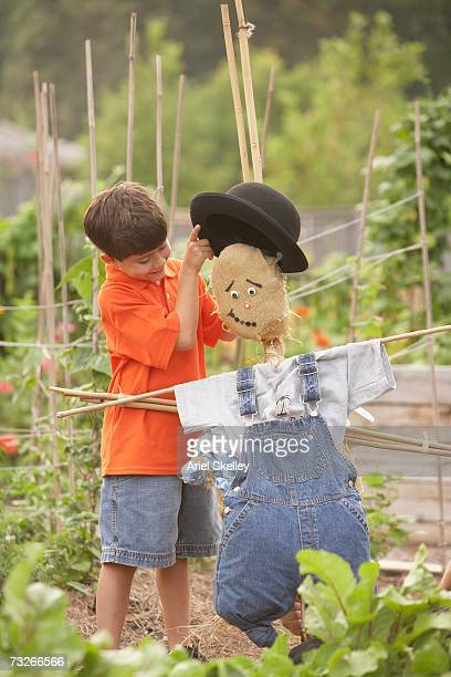 Young Hispanic boy putting hat on scarecrow