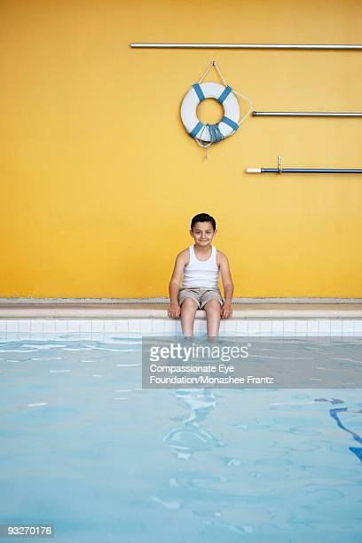 "young hispanic boy seated on edge of pool. - ""compassionate eye"" fotografías e imágenes de stock"