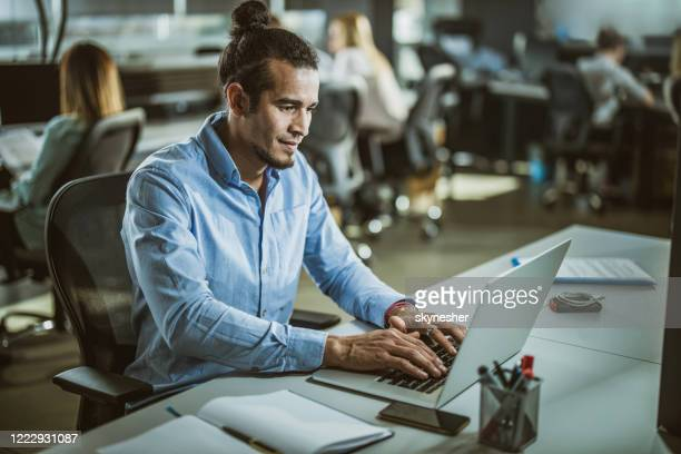 young hispanic businessman working on a computer in the office. - incidental people stock pictures, royalty-free photos & images