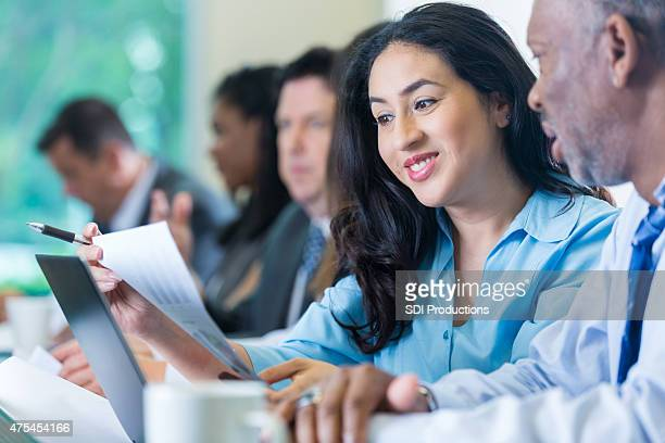 Young Hispanic businesswoman reviewing financial information during conference