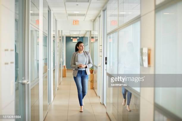 コワーキングオフィスを歩く若いヒスパニックビジネスウーマン - 接近する 女性 ストックフォトと画像