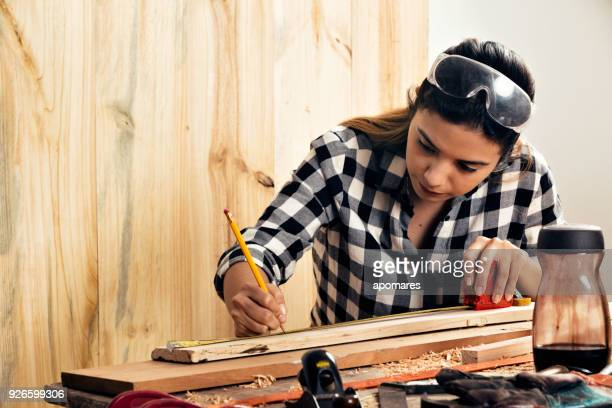 Young Hispanic carpenter woman measuring on wood planks home workshop